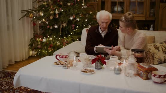 Thumbnail for Grandfather Talking While Granddaughter Holding Digital Tablet