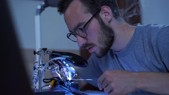 Thumbnail for Portrait of Skill Young Bearded Man in Glasses Working with a Soldering Iron at His Working Place
