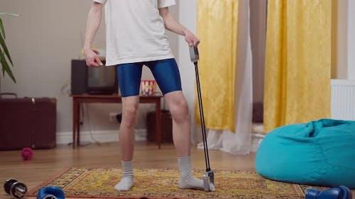 Unerkennbarer dünner Retro-Mann macht Aerobic mit Widerstandsband drinnen