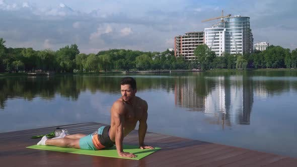 Handsome Guy with Bare Chest Stretching Body on Yoga Mat