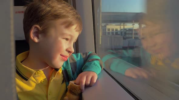 Thumbnail for Little Boy Looks Out the Train Window and Holds a Toy