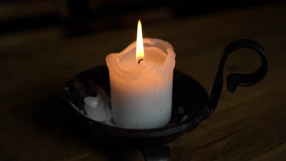 Thumbnail for Candle in a Candlestick on a Wooden Table