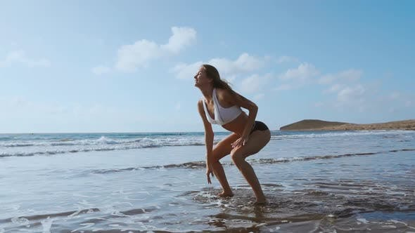 Thumbnail for Girl in Sportswear Shorts and T-shirt Performs Jumps with Squats on the Beach Near the Ocean