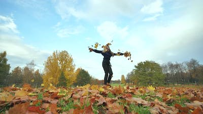 A Young Girl Schoolgirl Whirls with Autumn Leaves in the City Park