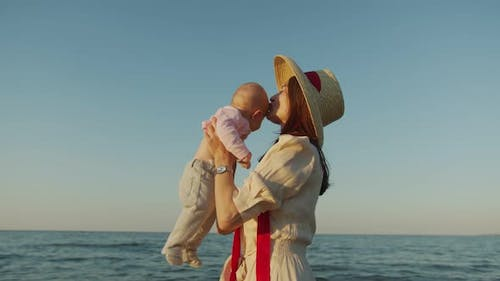 Young Mother Holding Her Baby in Front of Her at the Sea