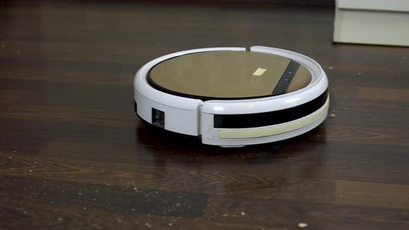 Thumbnail for The Robot Vacuum Cleaner Is Cleaning the Room. A Round Vacuum Cleaner Automatically Drives Around
