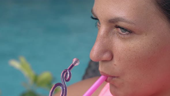 Thumbnail for Pretty Lady Sips Tasty Cocktail Through Pink Plastic Straw