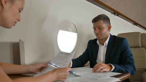Thumbnail for Two Business People Inside of Luxury Jet Cabin Sign Documents.