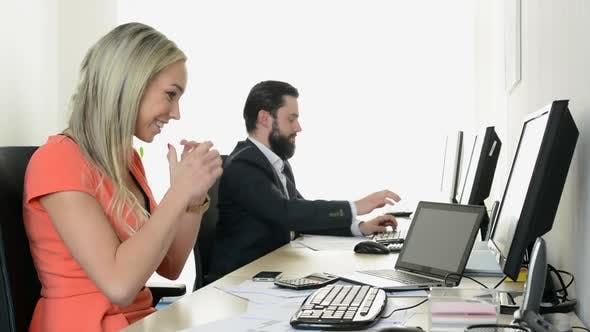 Thumbnail for Woman Rejoices and Man Works on Desktop Computer in the Office