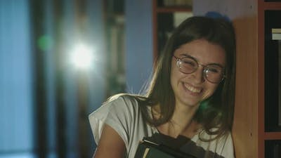 Girl in Glasses with Books in Hands and Leaning on Bookshelf Laughs in Library
