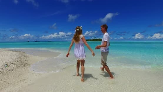 Thumbnail for Beautiful people on honeymoon vacation have fun on beach on sunny white sandy background 4K