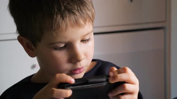 Thumbnail for Boy Playing Video Game on Mobile Phone. Young Hacker. Cyber Security Background. Child and Gadget