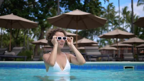 Caucasian Woman in a White Swimsuit and Wears Her Sunglasses While Standing in a Swimming Pool