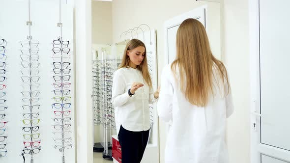 Thumbnail for Woman choosing eyeglasses. Young girl trying eyeglasses in front of mirror