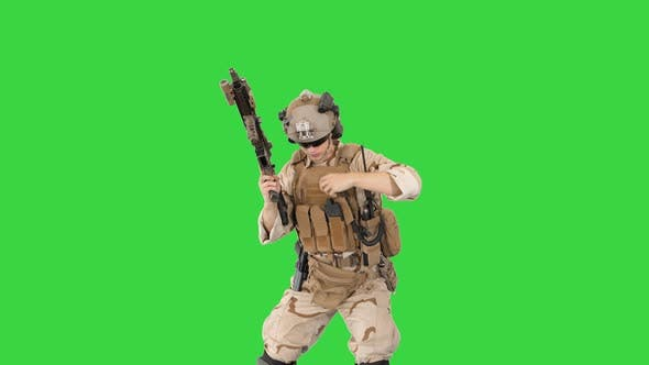 Soldier Shooting with Assault Rifle and Reloading on a Green Screen, Chroma Key.