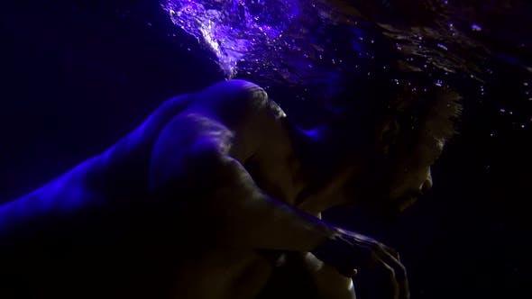 Sexy Naked Man Is Floating Underwater, Dark Swimming Pool, Subaquatic Shot