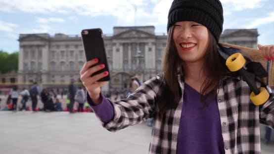 Thumbnail for Lovely millennial skater using technology to take selfie in London UK