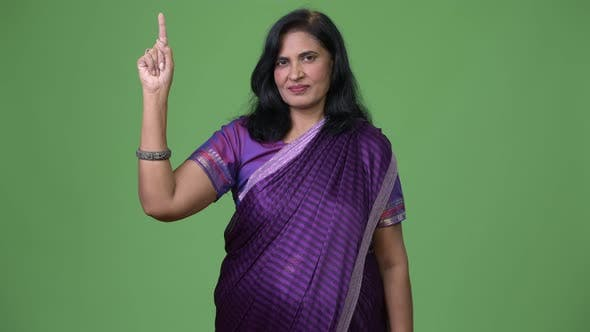 Cover Image for Mature Beautiful Indian Woman Pointing Up While Wearing Sari Traditional Clothes
