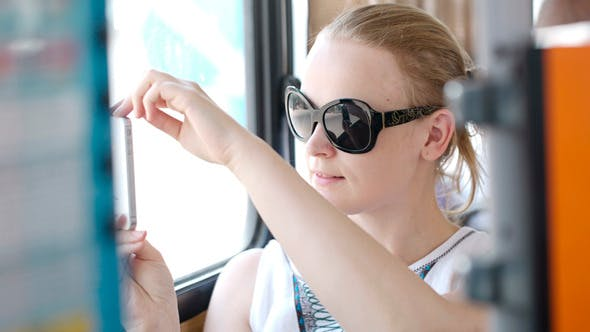 Thumbnail for Woman Taking Pictures At Her Mobile On A Bus