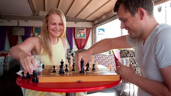 Cover Image for Smiling Couple Playing A Game Of Chess
