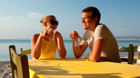 Thumbnail for Young Couple Enjoying Drinks At The Seaside