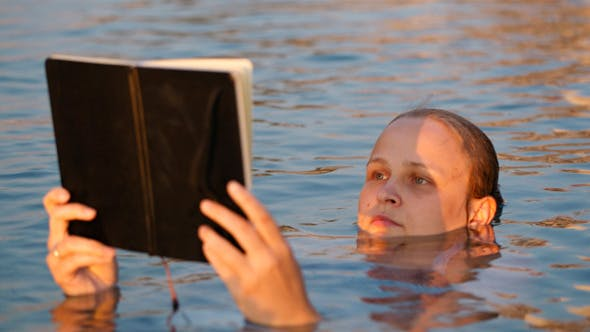 Thumbnail for Woman Reading While Floating In The Sea