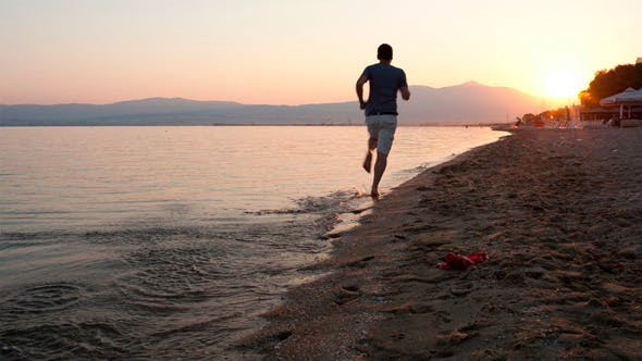 Thumbnail for Man Running Along A Beach At Sunset