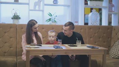 Toddler Takes Talking Father Ear and Kisses in Restaurant