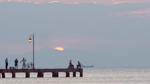 Thumbnail for People Relaxing On A Pier At Sunset