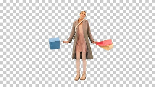 Young woman in a coat rotating with shopping bags, Alpha Channel