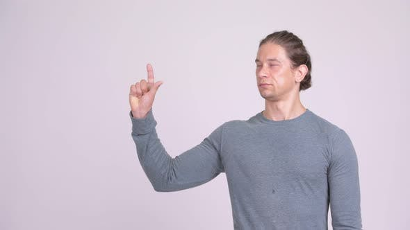 Cover Image for Handsome Man Thinking While Pointing Finger Up Against White Background