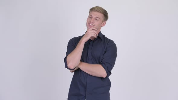 Thumbnail for Young Happy Blonde Businessman Smiling and Thinking