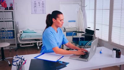 Healthcare Assistant Taking Notes on Clipboard Working in Hospital