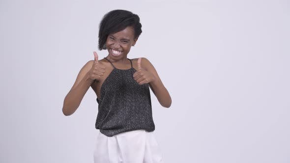 Cover Image for Happy Young African Woman Looking Excited and Giving Thumbs Up