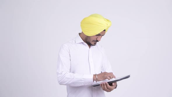 Thumbnail for Happy Bearded Indian Sikh Businessman Using Digital Tablet and Getting Good News