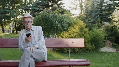Mustachioed Senior Man Having Emotional Dispute on Web Cam on Bench in Park