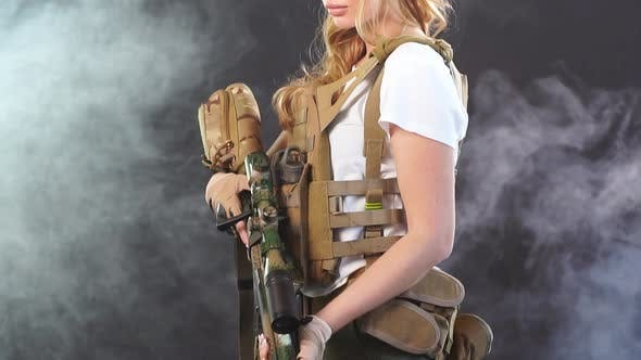 Thumbnail for Beautiful Woman in Military Outfit Holding Weapon in Hands Stands in Smoky Background. Slow Motion