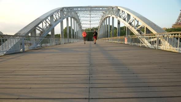 Thumbnail for A couple running across a bridge
