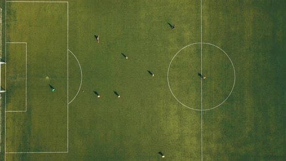 Aerial View of Football Team Practicing at Day on Soccer Field in Top View