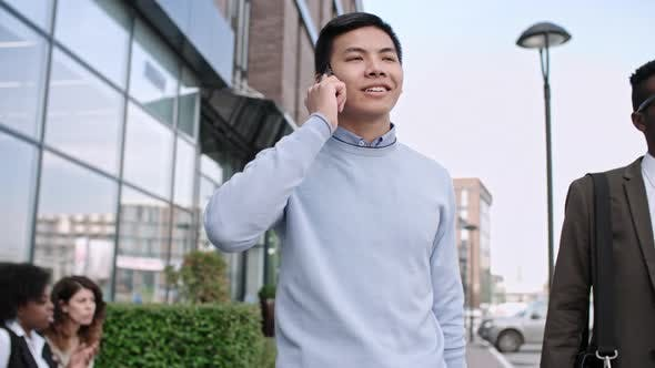 Thumbnail for Young Asian Businessman Standing on Street and Talking on Phone
