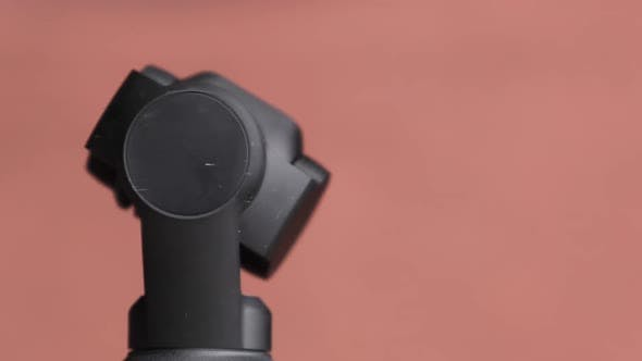 Mechanical Gimbal Camera Lens Rotates on Red Background Robotic Camera Macro