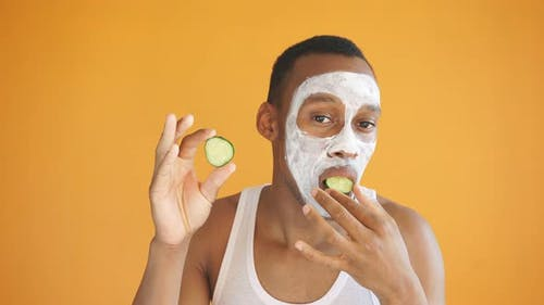 Positive African American Applies a White Face Mask with Cucumber Slices, Expresses Positive