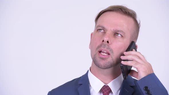 Thumbnail for Happy Blonde Businessman Thinking While Talking on the Phone