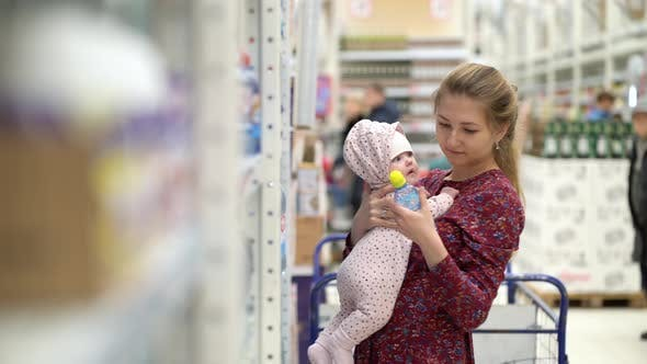 Thumbnail for Woman Choosing Children Food with Little Baby Child Girl on Hands During Supermarket Shopping