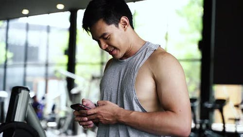 Asian Sportsman Using a Mobile Phone at Gym