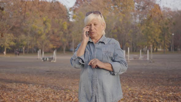 Thumbnail for Mature European Woman Standing in the Autumn Park and Talking By Smart Phone. Positive Senior