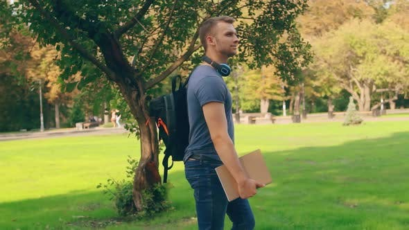 Thumbnail for Guy Wearing Casual Clothes Walks in City Park
