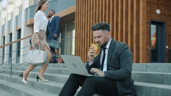 Slow Motion of Male Office Worker Using Laptop and Eating Sandwich Sitting on Stairs Outside Office