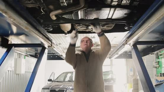 Thumbnail for Smiling Mature Mechanic Man In A Car Service. Portrait Under The Car