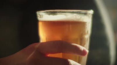 Hand tapping on a glass of beer